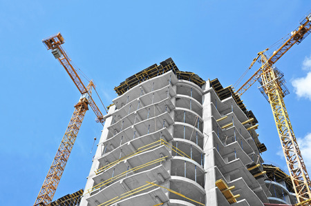 40545183 - crane and building construction site against blue sky
