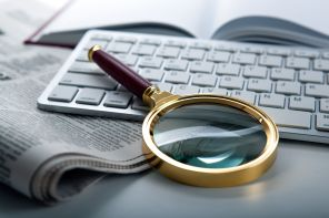 62232853 - magnifier and newspaper on the keyboard closeup