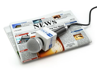 49190850 - news or journalism concept. microphone on the newspaper isolated on white. 3d